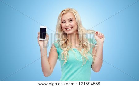 emotions, expressions, technology and people concept - smiling young woman or teenage girl showing blank smartphone screen over blue background
