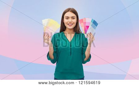 color scheme, decoration, design and people concept - smiling young woman with color swatches or samples over pink and violet background