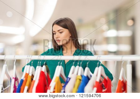 nothing to wear, clothing, sale, fashion and style concept - woman choosing clothes at shopping center or mall
