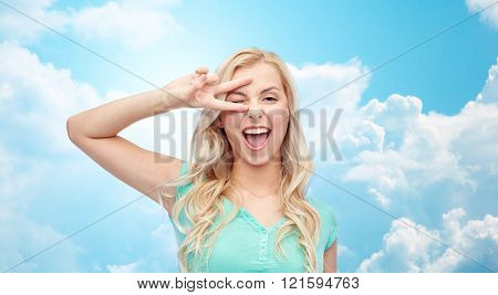 emotions, expressions, gesture and people concept - smiling young woman or teenage girl showing peace hand sign over blue sky and clouds background