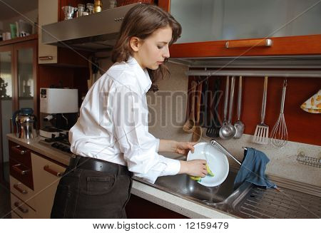 Young woman washing dishes in a kitchen sink