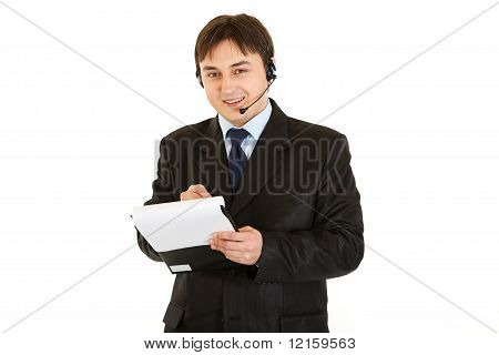 Smiling modern businessman with headset making notes in document isolated on white