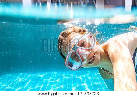 9 years old child wearing diving mask swimming in the pool, underwater shot