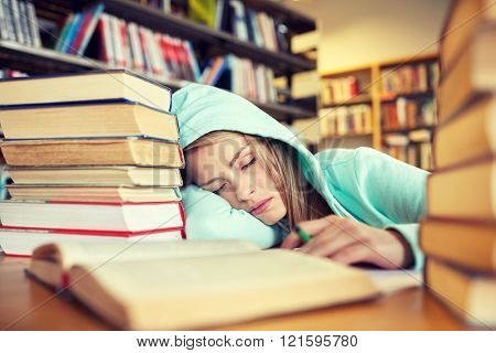 people, education, session, exams and school concept - tired student girl or young woman with books sleeping in library