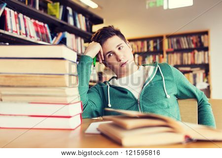 people, knowledge, education, literature and school concept - bored student or young man with books dreaming in library
