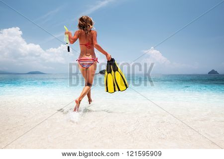 Young woman running into the tropical sea with fins and snorkeling gear