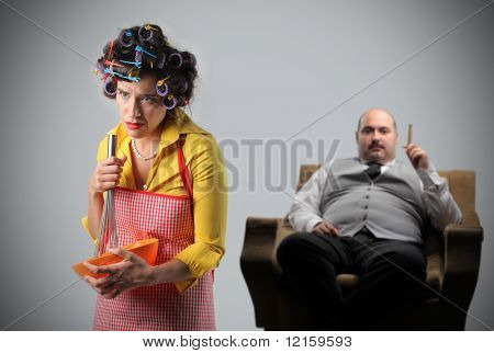 Tired housewife preparing food and overweight man sitting in an armchair
