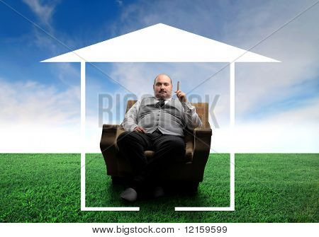 Overweight man sitting in an armchair on a green meadow surrounded by the form of a house