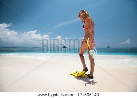 Young woman standing on the beach with fins and snorkeling gear