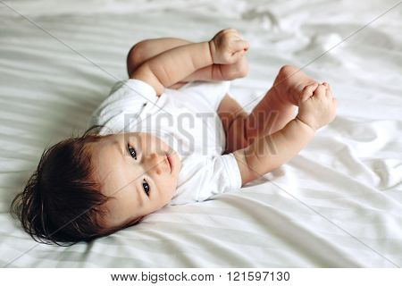 Portrait of a cute 4 months old baby lying down on a bed