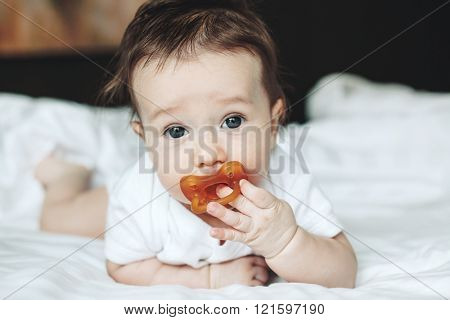 Portrait of a cute 4 months old baby with nipple lying down on a bed
