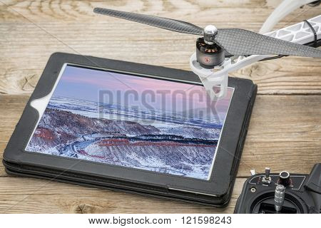 drone aerial photography concept - reviewing aerial picture of Colorado foothills and plains on a digital tablet with a drone rotor and radio control transmitter,