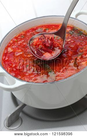 serving borscht ( beet soup ) with a ladle, russian ukrainian cuisine
