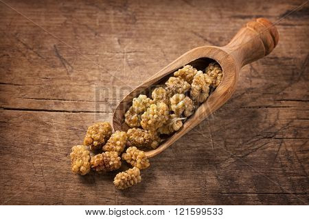 Mulberries in a spoon on a wooden background