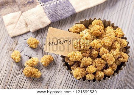 Mulberries in a bowl on a wooden background
