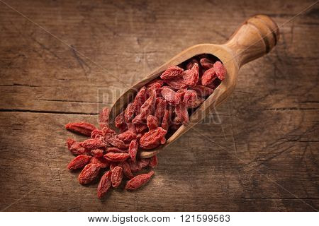 Goji berries in a spoon on a wooden background