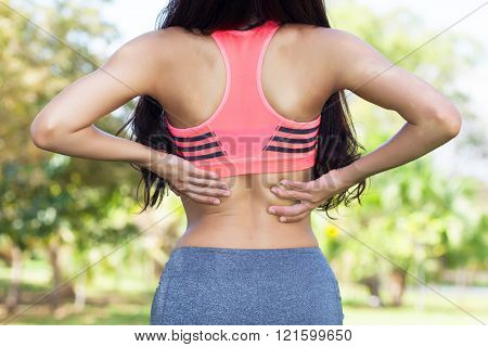 Back pain. Athletic woman in pink sportswear standing and rubbing the muscles of her lower back