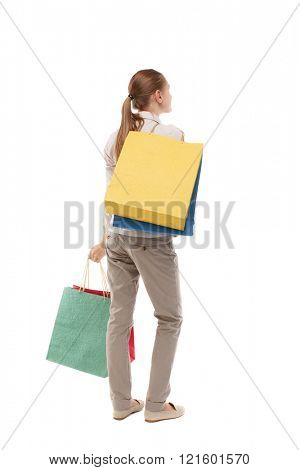 back view of woman with shopping bags . beautiful brunette girl in motion. Isolated over white background. Girl in light trousers standing with a variety of paper bags.