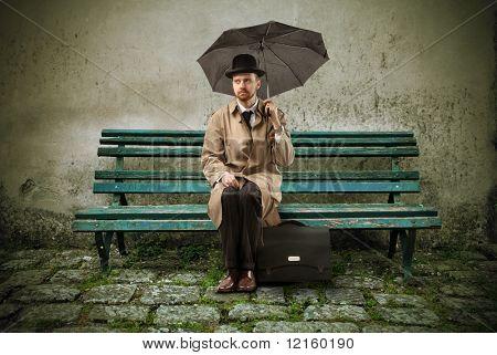 Cavalheiro com guarda-chuva, sentado em um banco de parque de madeira