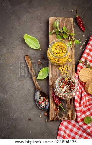Mix of different peppers in a jars of glass, red pepper, black pepper, white pepper, hot pepper and basil. Food background, Top view