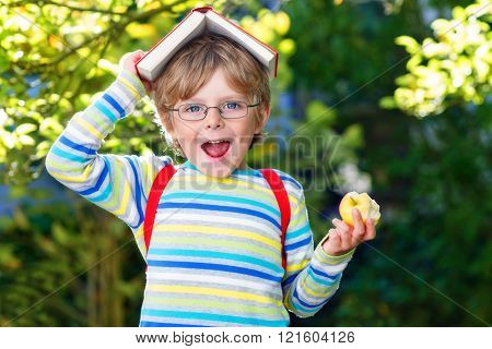Little kid boy with apple on way to school