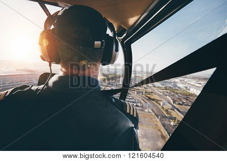 Pilot Flying A Helicopter Over A City