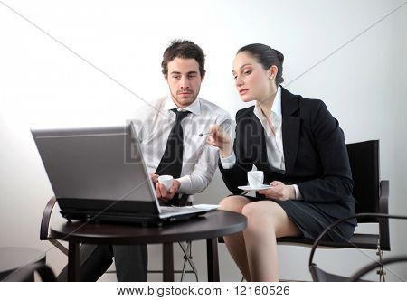 Business people sitting and discussing in front of a laptop with a cup of coffee