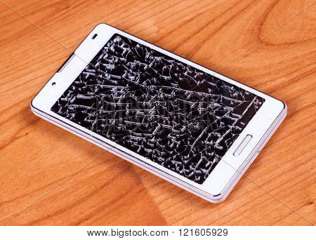 Broken Mobile Phone On Wood Ground