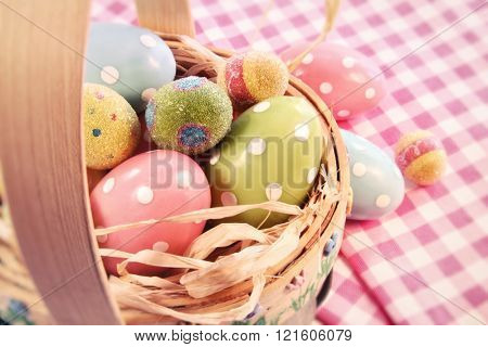 Different color eggs in a easter basket on table