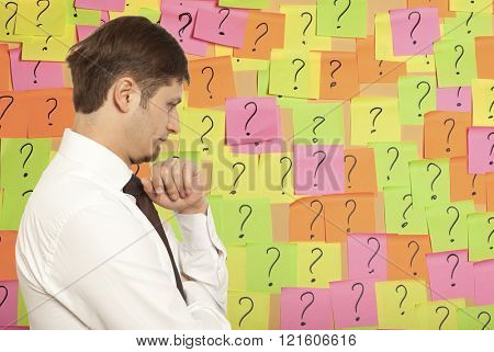 Businessman thinking with question marks written on adhesive notes stuck