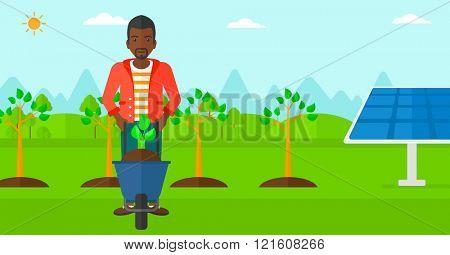 Man with plant and wheelbarrow.