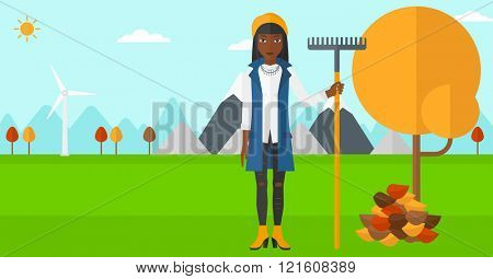 Woman with rake near tree and heap of leaves.