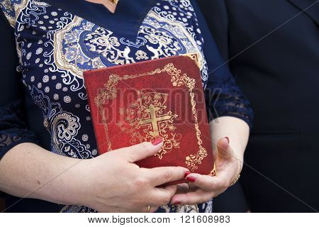 Orthodox Christian with a Bible in his hand. A believer in Jesus Christ elderly  woman. Faith in God and hope. A parishioner of the Church. Easter.