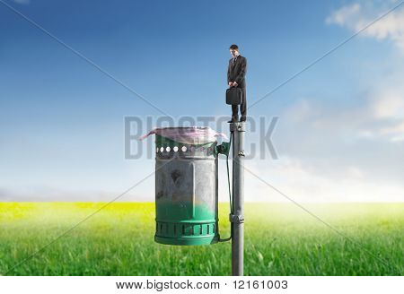 Businessman standing on a trash bin on a green meadow