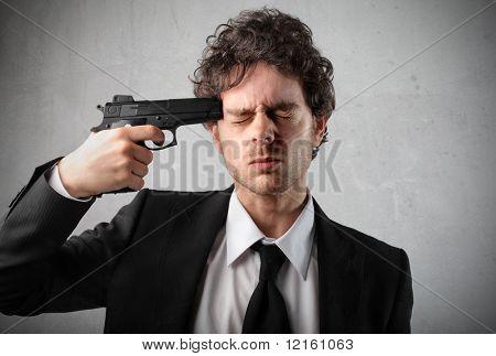 Young man pointing a gun at his head