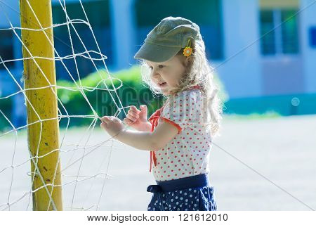 Nursery school girl playing near football goal net with yellow goalposts