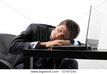 Businessman sleeping on the keyboard of a laptop
