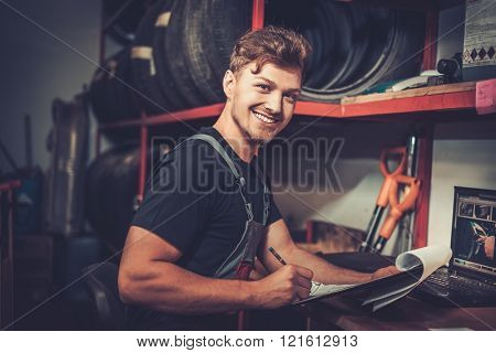 Professional car mechanic at his workplace preparing checklist in auto repair service.