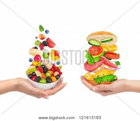 the choice of a healthy food or unhealthy food. Fruit salad keeps the hand and the sandwich holds in his hand isolated on a white background. The concept of diet.