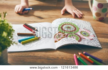 Child paint a coloring book. New stress relieving trend. Concept mindfulness, relaxation.