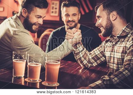 Cheerful old friends having fun arm wrestling each other in pub.