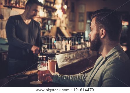Stylish man sitting alone at bar counter with a pint of light beer.