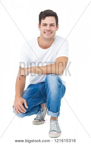 Handsome man crouching on white background