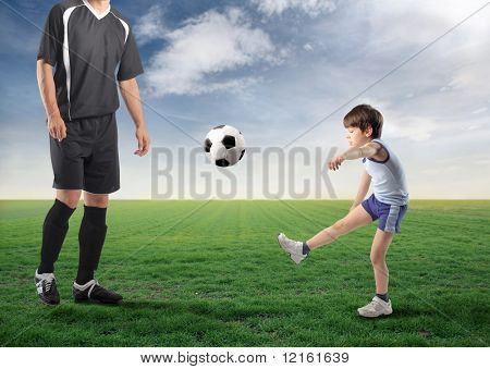 Child playing football on a green meadow with older man next to him