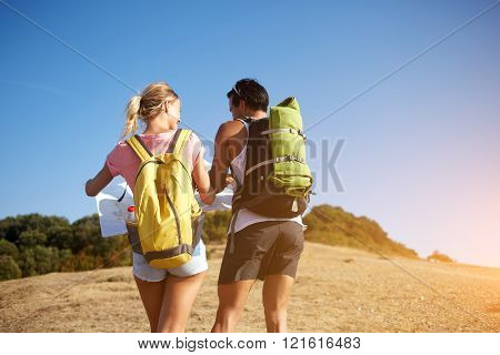 Back view of a happy smiling man and woman wanderers are holding map while standing on high hill in sunny day young couple of a hikers are laughing to each other during their walking in the fresh air