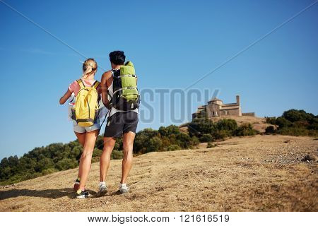 Back view of a two backpackers are exploring location map while standing on a high hill against beautiful blue sky man and woman wanderers are walking together in mountains during their summer trip