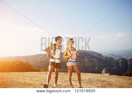 Full length portrait of a young man and woman travelers with rucksacks on backs are admiring wonderful landscape while standing on high mountain in sunny summer day during their joint vacations abroad