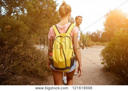 Back view of a young two travelers are walking in rural during their amazing summer weekend man and woman wanderers are hiking with rucksacks in mountains during their wonderful adventure overseas