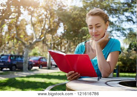 Charming woman is reading interesting book while sitting outdoors in park in summer day during spare time beautiful Caucasian female is enjoying recreation and rest during her spring weekend abroad