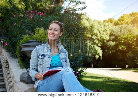 Happy gorgeous woman is enjoying beautiful warm day and spare time while is sitting in green nice park young cheerful Caucasian female is smiling to someone while is relaxing outdoors with book